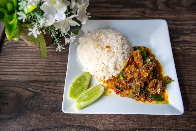 Stir fried deep fried catfish with curry paste and rice Premium Photo