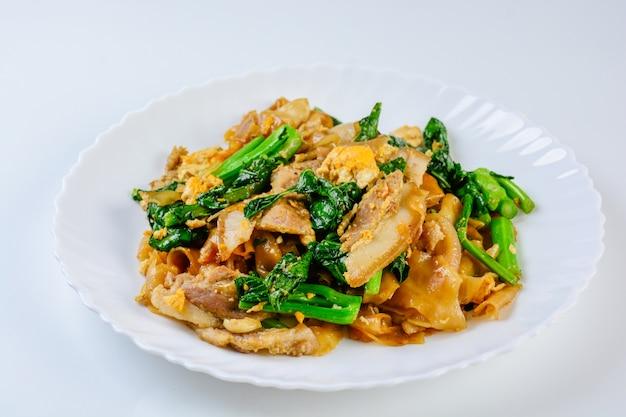 Stir-fried fresh rice-flour noodles with sliced pork, egg and kale. quick noodle stir-fry. Premium Photo