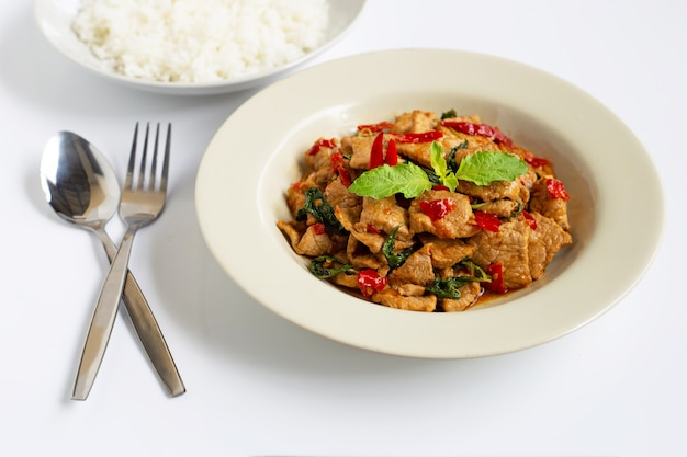 Stir-fried hot and spicy pork with holy basil on white Premium Photo
