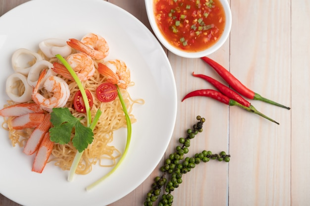 Stir-fried instant noodle with prawn and crab stick along in a white dish. Free Photo