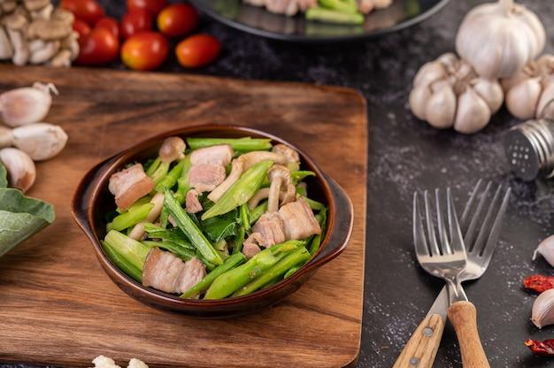 Жареная капуста и свиная грудинка в тарелке на деревянной тарелке. Бесплатные Фотографии