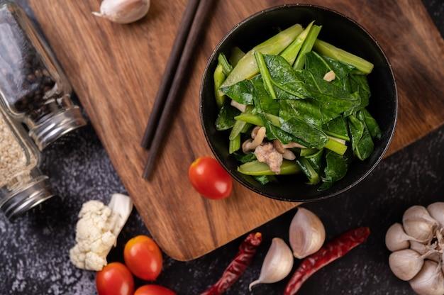 Cavolo cappuccio e pancetta di maiale saltati in padella in un piatto posto su un piatto di legno. Foto Gratuite