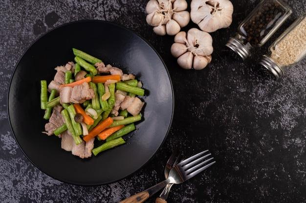長豆とにんじんを炒め、豚バラ肉を加え、黒皿にのせる。 無料写真