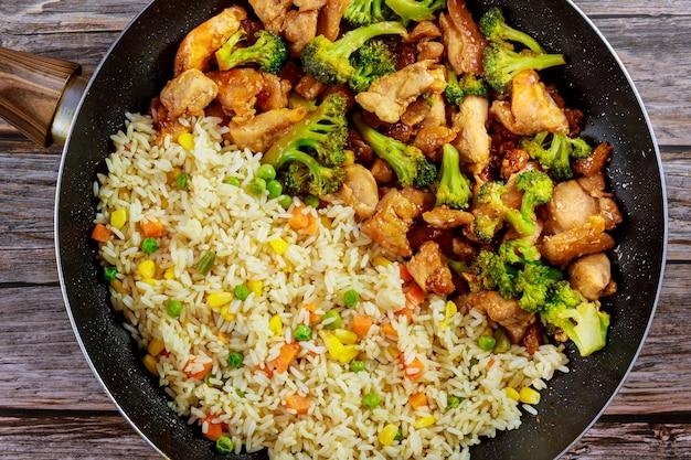 나무 배경에 냄비에 쌀과 닭고기와 브로콜리 볶음. 공간을 복사하십시오. 프리미엄 사진
