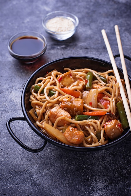 Stir fry noodles with chicken, tofu and vegetable. Premium Photo