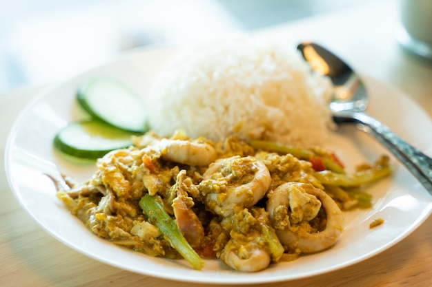 Stir fry squid with curry on the cooked rice Premium Photo