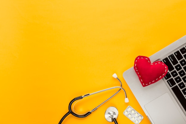 Stitched heart shape on laptop with stethoscope; blister packed tablet on yellow background Free Photo