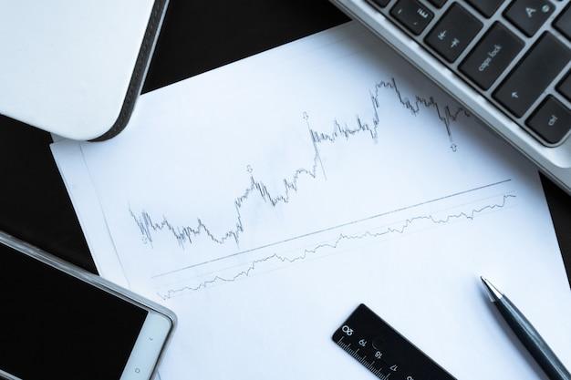 Диаграмма запасов и канцелярские товары на столе Premium Фотографии