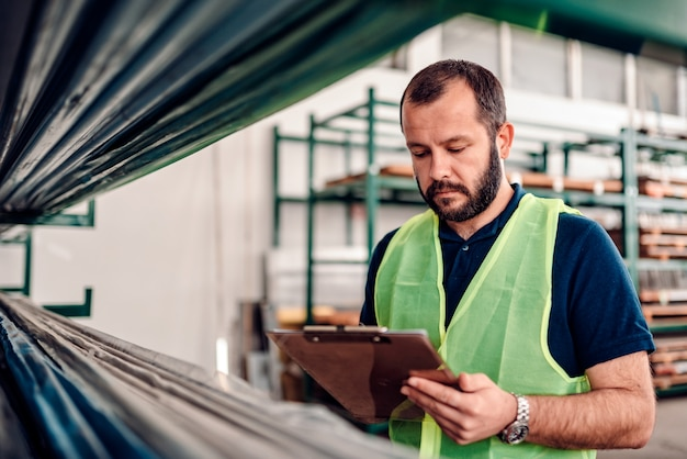 Stock clerk processing order for shipment in the warehouse factory Premium Photo