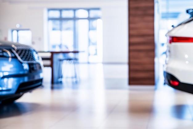 背景がぼやけている自動車ディーラーのショールームにある車の在庫。セレクティブフォーカス Premium写真