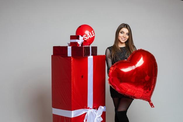 包まれたプレゼントの横に立っている赤いハート型の風船を保持している黒いドレスのブルネットの少女のストックフォト。ギフトの上にセールワードが付いた気球。 無料写真