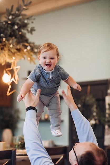 父が家で彼と遊んでいる間、空中で陽気な少年のストックフォト。お父さんは息子を空中に投げ上げて捕まえました。赤ちゃんは笑っています。バックグラウンドでのクリスマスの装飾。 Premium写真