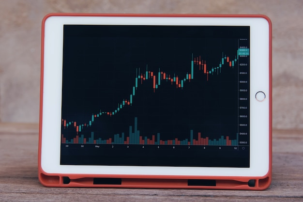 Stock trading forex on tablet on a wooden table Premium Photo