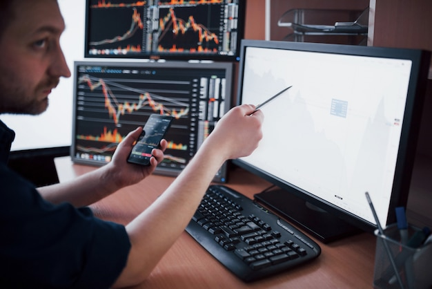 Stockbroker in shirt is working in a monitoring room with display screens. stock exchange trading forex finance graphic . businessmen trading stocks online Premium Photo