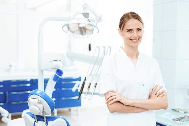Stomatology clinic. smiling nurse posing against. Premium Photo