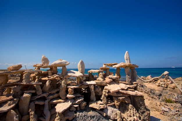 Stone figures on beach shore of illetes beach in formentera Premium Photo