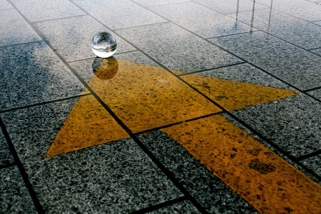 Un terreno di pietra con una freccia gialla che punta verso la bal di cristallo Foto Gratuite