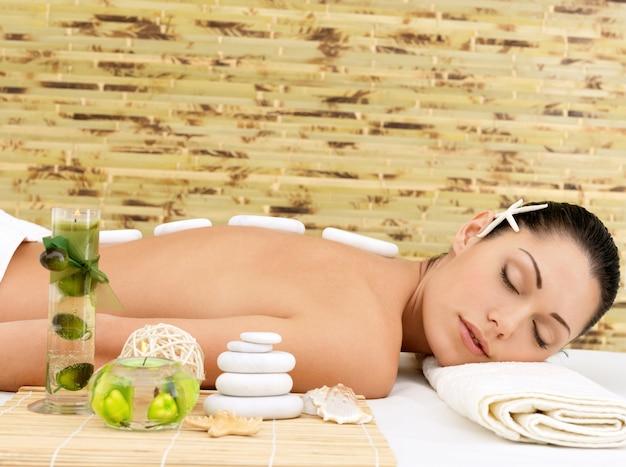 Massaggio con pietre per giovane donna al salone di bellezza spa. terapia ricreativa. Foto Gratuite