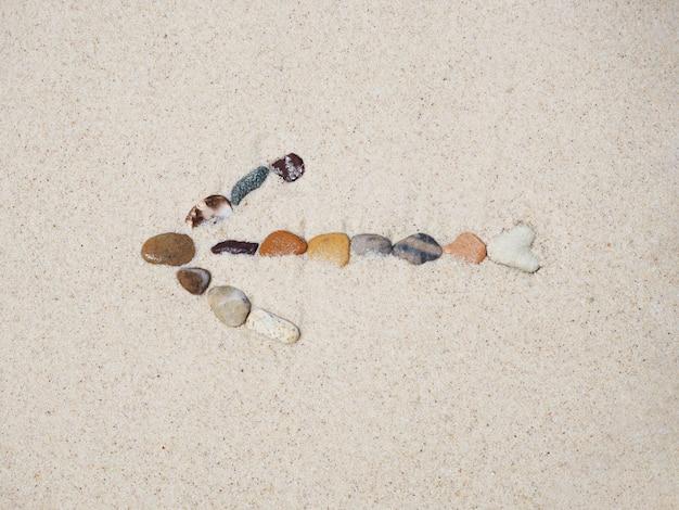 Stones arrow sign on beach sand. Premium Photo