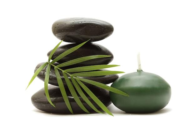 Камни, зеленые листья и свеча на белом фоне Premium Фотографии