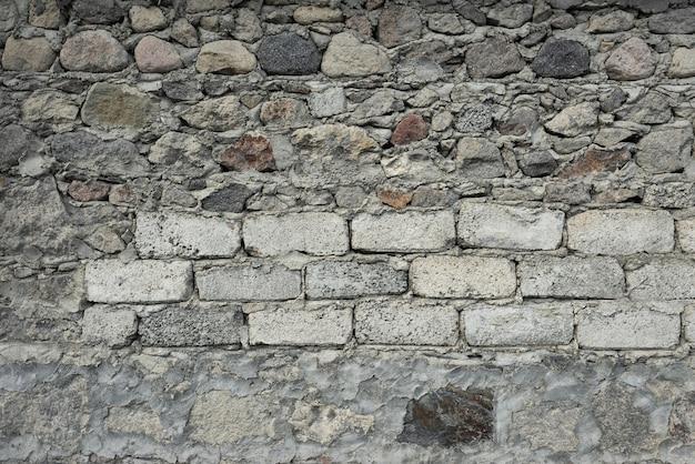 さまざまなサイズと形の石が互いに重なり合っています。それらの間のセメント。 t Premium写真