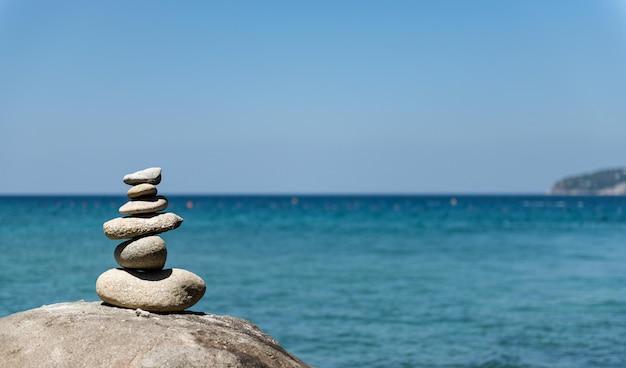 Stones pyramid on pebble beach symbolizing stability, zen, harmony, balance. Premium Photo