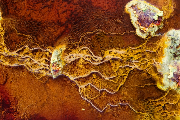 Stones in red waters connected by yellow stromatolites Premium Photo