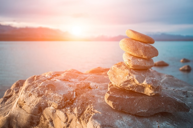 Stones stacked in the sea at sunset Free Photo