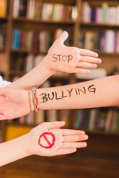 Stop bullying message on children's arms Free Photo