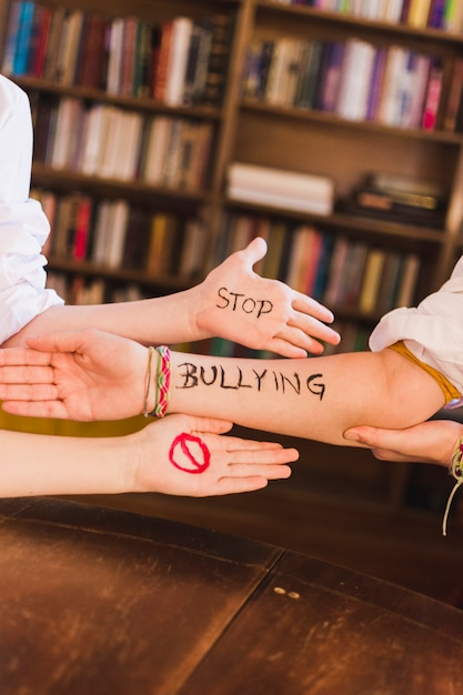 Stop bullying slogan on children's arms Free Photo