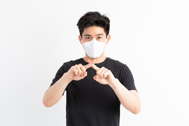 Stop civid-19, азиатский мужчина в маске показывает жест рукой, чтобы остановить вспышку вируса короны Бесплатные Фотографии