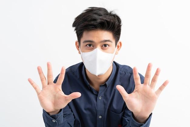 ストップシビッド-19、フェイスマスクを身に着けているアジア人男性は、コロナウイルスの発生を止めるためのストップハンドジェスチャーを示しています 無料写真