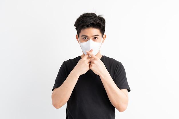 Stop civid-19, uomo asiatico che indossa la maschera per il viso mostra il gesto delle mani per fermare l'epidemia di virus corona Foto Gratuite