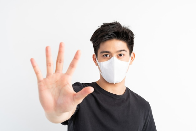 Stop civid-19 , asian man wearing face mask show stop hands gesture for stop corona virus outbreak Free Photo
