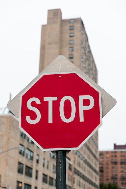 Стоп дорожный знак с размытым фоном здания Premium Фотографии