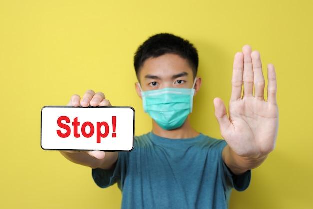 パンデミックコロナウイルスについての誤ったニュースを共有するのをやめなさい、コロナウイルスのデマを共有するために停止ジェスチャーをしている若いアジア人、黄色で隔離 Premium写真