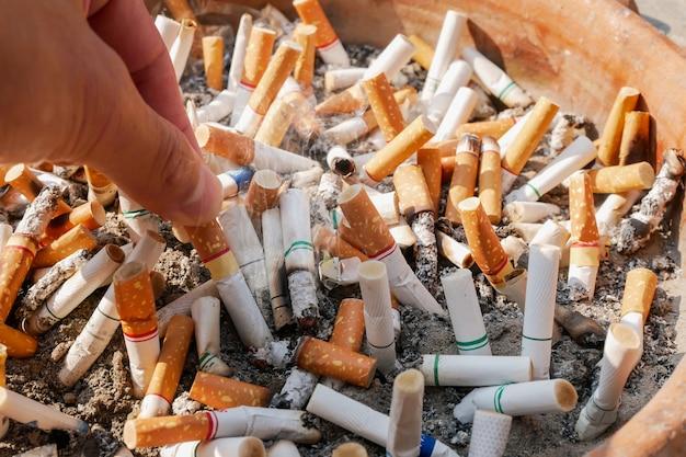 今日の喫煙をやめ、手持ちのタバコの吸い殻を背景の多くのタバコの吸い殻に入れます Premium写真