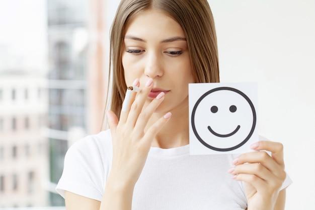 喫煙をやめる、壊れたタバコと笑顔でカードを保持している女性 Premium写真