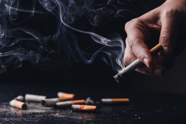Stop smoking .world no tobacco day.close up a hand holding a crumpled, smoldering cigarette with smoke hand smoking cigarette ,unhealthy lifestyle Premium Photo