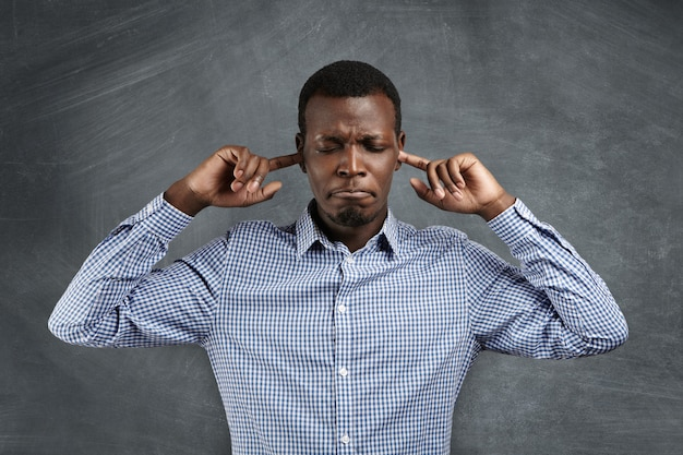 Stop this sound! portrait of angry and frustrated african man in shirt stopping his ears, plugging them with fingers, closing eyes and pursing lips while suffering from loud noise. negative emotions Free Photo