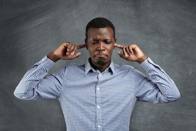 この音を止めろ!シャツを着た怒りと欲求不満のアフリカ人の肖像画。耳をふさぎ、指でつないだり、目を閉じたり、大きな音に悩まされながら唇をすぼめたりしています。否定的な感情 無料写真