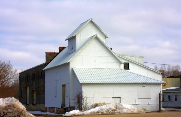 曇った青い空を背景にした倉庫 無料写真