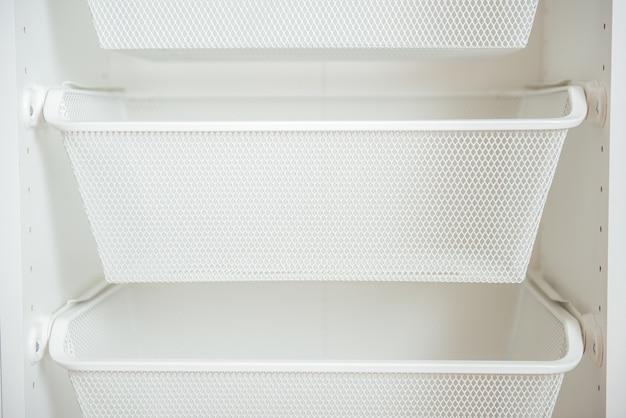 Система хранения: белые пустые металлические корзины для одежды в гардеробной Premium Фотографии