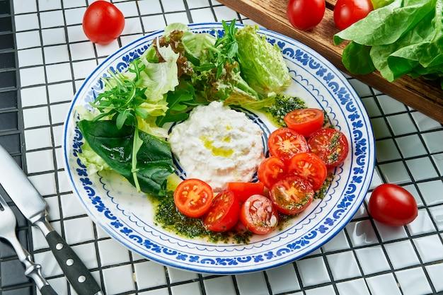 Закройте вверх по взгляду на аппетитном салате с итальянским сыром strachatella, салатом, томатами черри в красивой голубой керамической плите на белой таблице. вкусная еда. плоская планировка Premium Фотографии