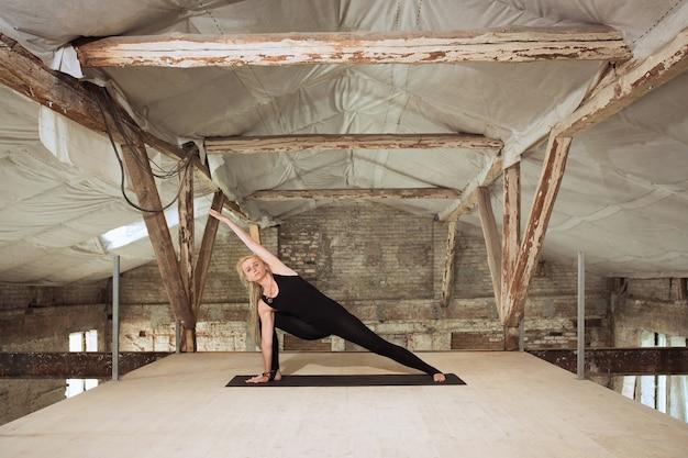 Dritto. una giovane donna atletica esercita lo yoga su un edificio abbandonato. equilibrio della salute mentale e fisica. concetto di stile di vita sano, sport, attività, perdita di peso, concentrazione. Foto Gratuite