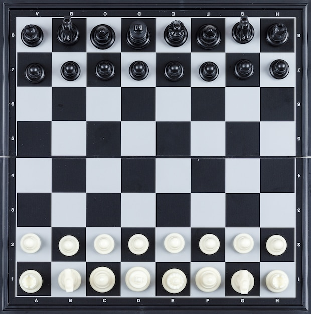 Strategy and chess concept with chess figures on checkerboard  top view. Free Photo
