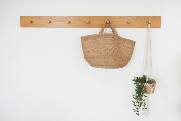 Straw bag on a hanger in the scandinavian style hall Premium Photo