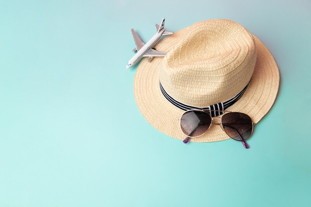 Straw beach hat, sunglass and white airplane in the summer Premium Photo