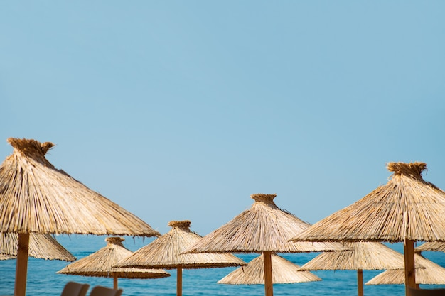 Straw beach umbrellas on a blue sky and sea background with a copy space Premium Photo