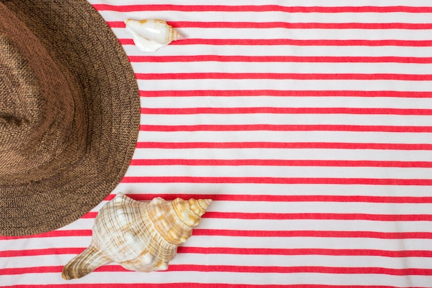 Straw beach woman's hat sun top view seashell with space for text. Premium Photo